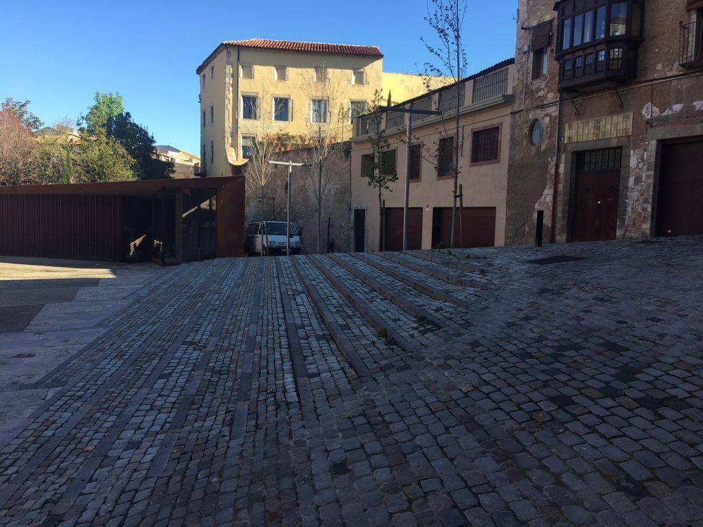 Pavimentación con adoquín recuperado y creación de tiras de pavimento con piedra de Girona