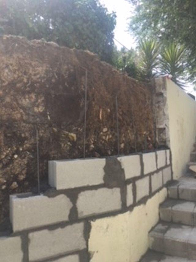 Derribo de muro agrietado y levantamiento de nuevo muro.
