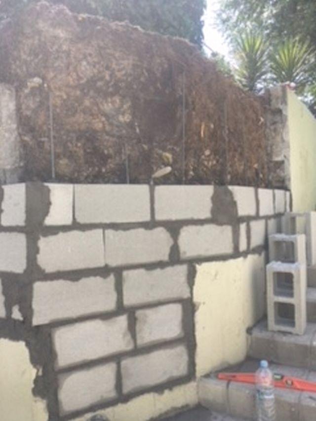 Levantamiento de muro de pared de bloque de cemento relleno de hormigón armado.