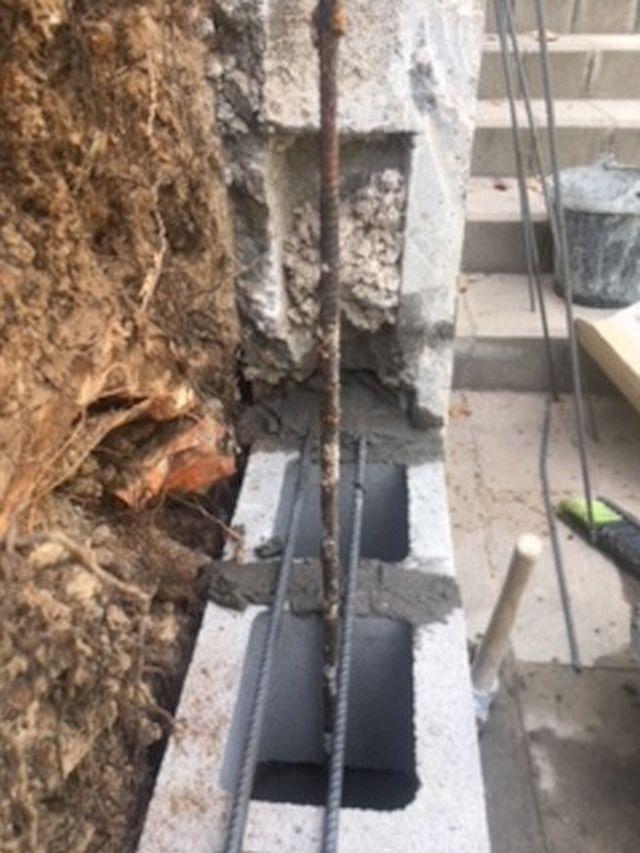 Muro de bloque de cemento relleno de hormigón armado.